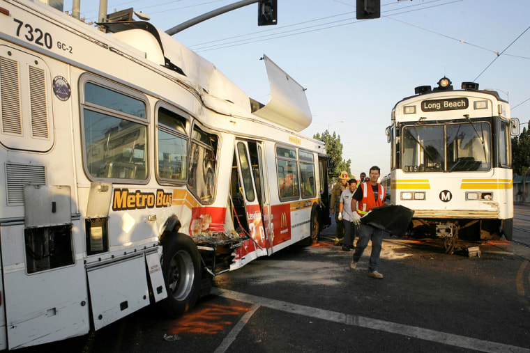 Emergency responders walk between the wreckage after alight-railtrain collided with an out-of-service bus near downtown Los Angeles on Friday.