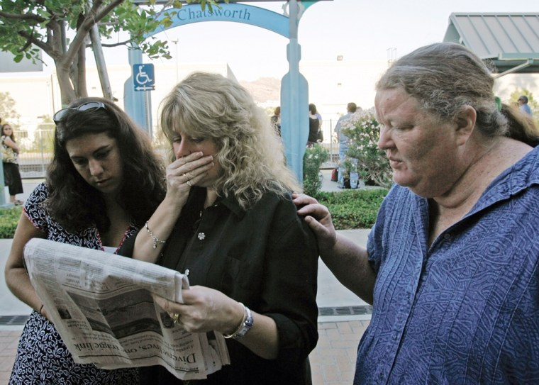 An unidentified commuter, left, and her companions, Melinda Moore, center, and Marianne Jones, right, react as they read names of fatalities from Friday's crash in the newspaper. They were waiting for a train Monday at the Chatsworth station.
