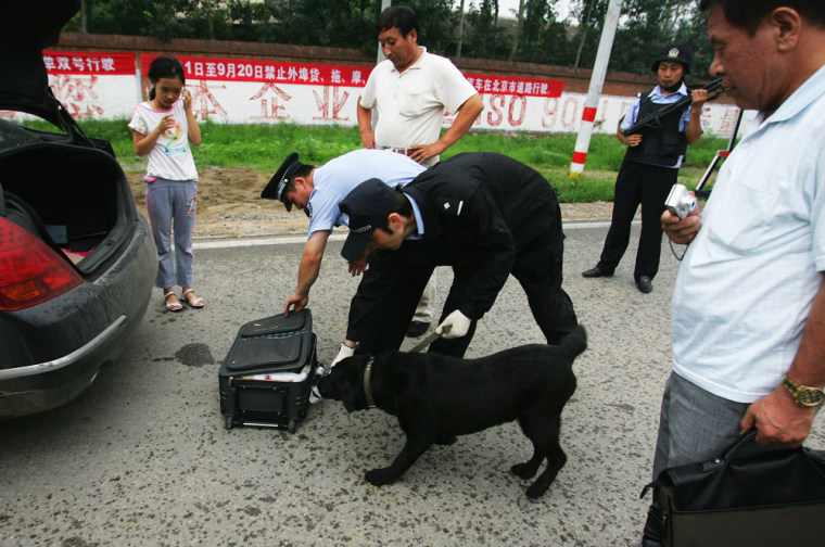 Image: Chinese policemen check passengers' bag as they inspect a vehicle at a checkpoint