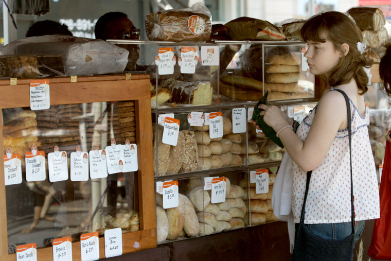 Valeria Zaitsevia buys bread at the Bread Alone organic whole grain bakery stand at the Union Square Farmers Market in New York.