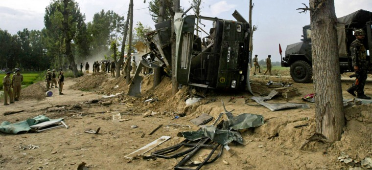 Soldiers stand near a vehicle damaged when anexplosion targeted Indian troops.