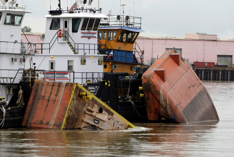 Image: Tug boats hold pieces of the barge