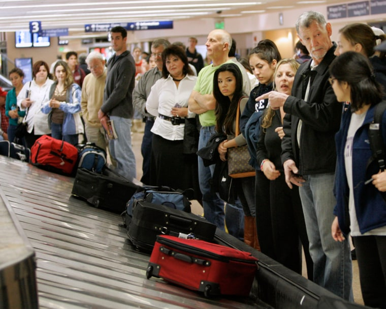 Image: Travelers line up to get their luggage
