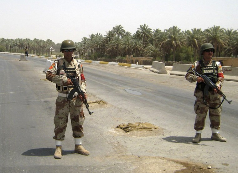 Image: Iraqi soldiers stand guard on a road in Baquba