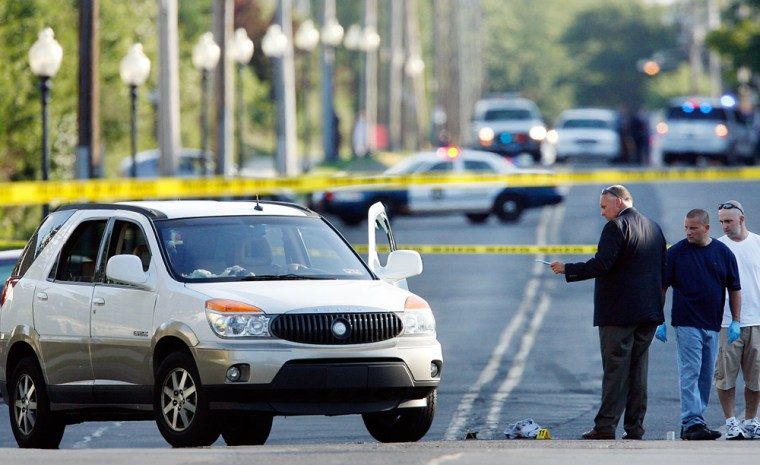 Investigators look at a late-model SUV with the driver's side window shattered in the Bristol Borough of Philadelphia, Friday. Two people are dead after a shooting outside a suburban Philadelphia book warehouse Friday.