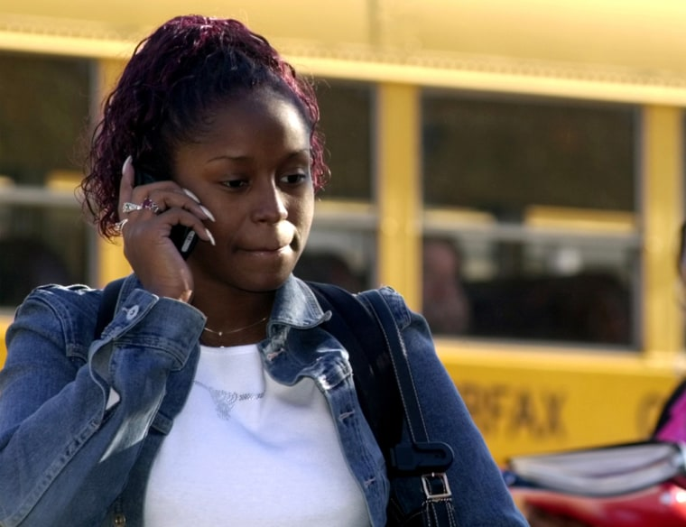Image: A girl speaks on a cell phone outside school