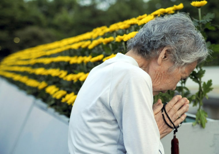 Image: An elderly Japanese woman prays in front of a monument at Hiroshima Peace Memorial Park