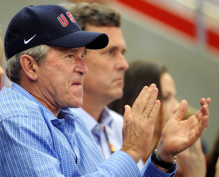 Image: US President George W. Bush reacts to watching the women's preliminary basketball match