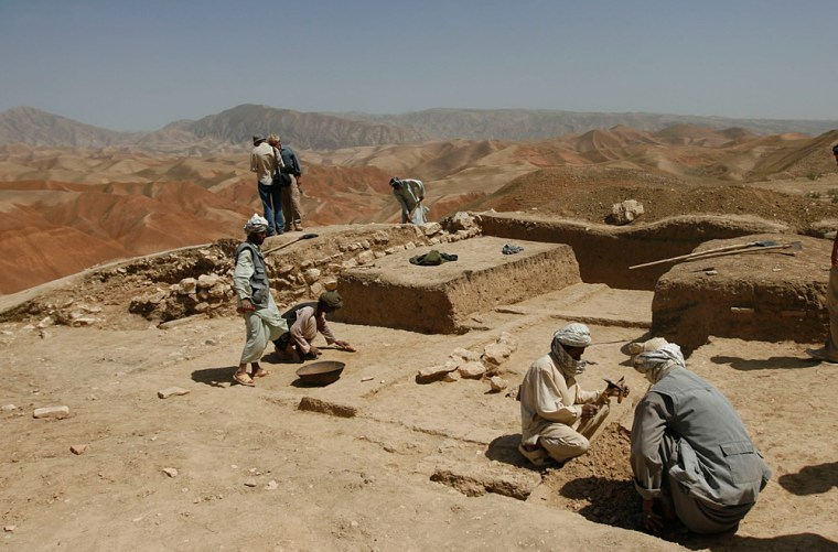 Afghan workers are seen digging the baked earth on the heights of Cheshm-e-Shafa in the Balkh province. Centuries-old shards of pottery mingle with spent ammunition rounds on a wind-swept mountainside in northern Afghanistan where French archaeologists believe they have found a vast ancient city lost to historical record.