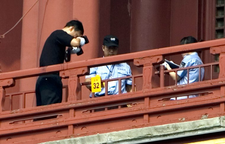 Image: A Chinese policeman takes pictures of the crime site