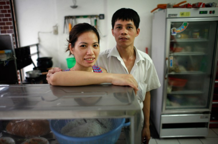 Ethnic Vietnamese and naturalized Taiwanese citizen Chen Shih Mei-ying, left, poses with her Taiwanese husband Lin Wen-jui in their food shop in Taipei, Taiwan.