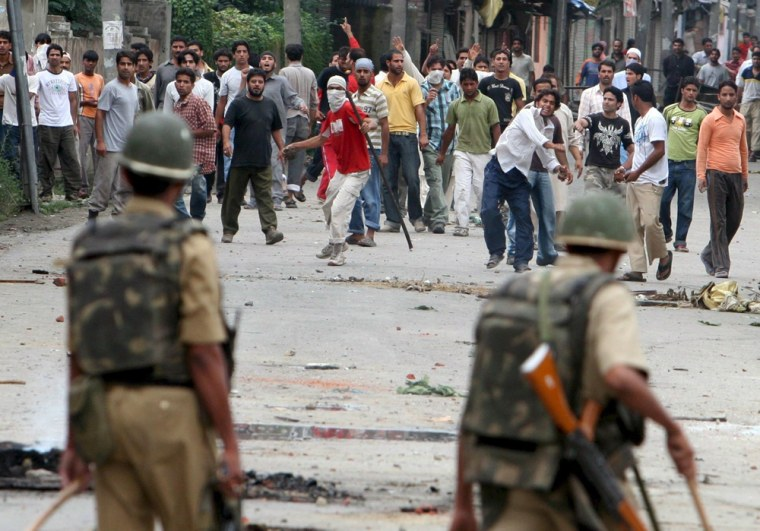 Image: Kashmiri Muslims shout slogans as they throw stones at Indian paramilitary soldiers
