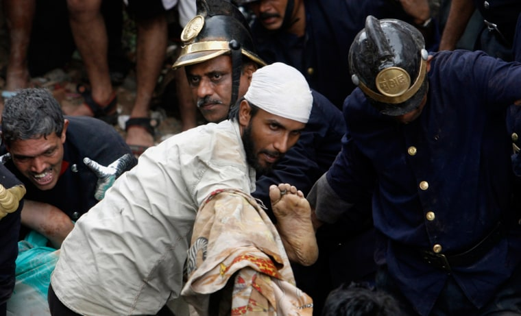 Image: Firemen and rescue workers carry the body of a victim out from the debris of a building that collapsed in Mumbai