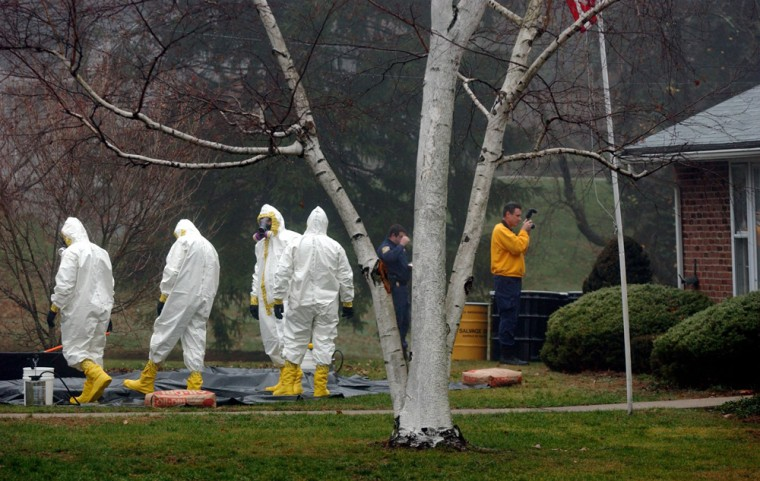 Image:   Adecontamination crew dressed in hazmat suits