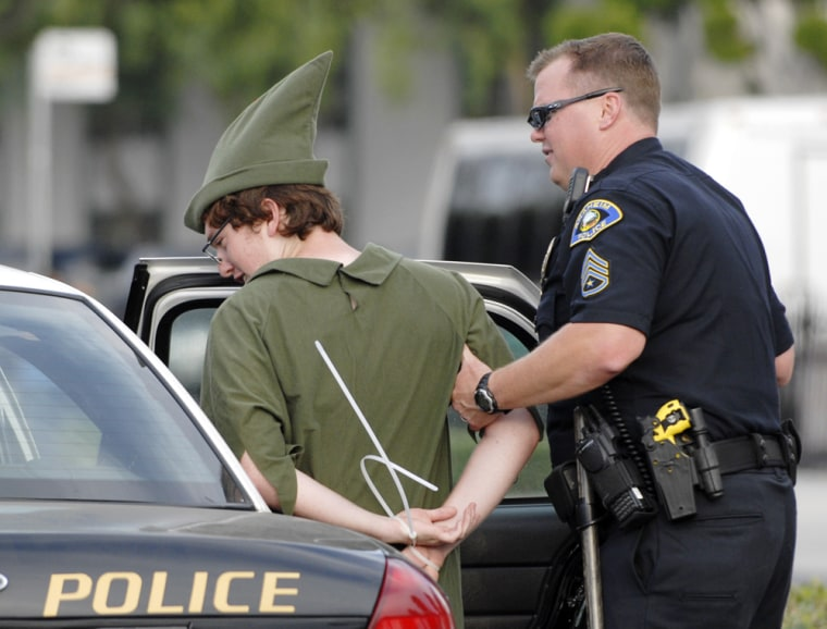 Image: A police officer with the Anaheim Police Department arrests a demonstrator dressed as Peter Pan