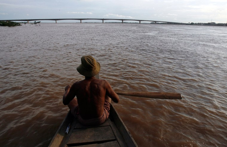 Cambodian man rows a boat  during floods near the Mekong river in Kampong Cham province