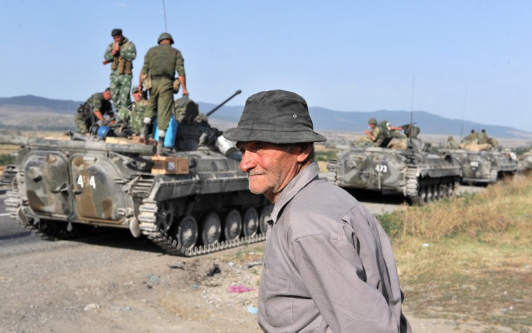 Image: An elderly Georgian man  looks at a convoy of Russian army APC's
