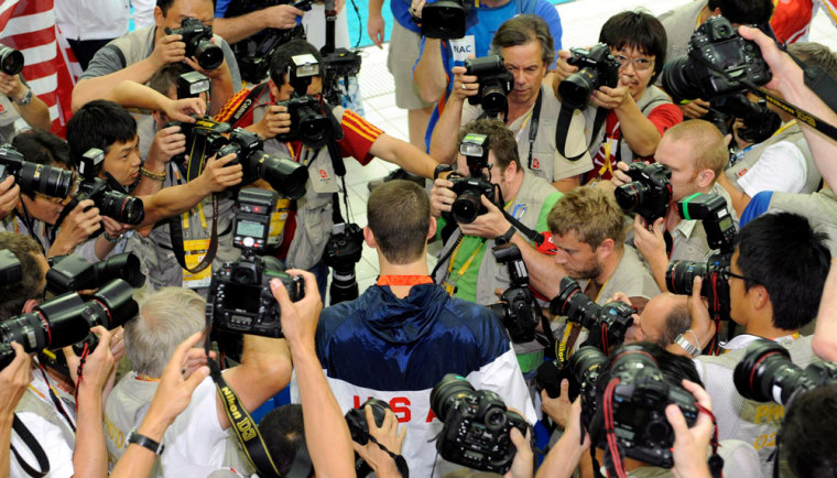 Image: Photographers surround US swimmer Michael Phelps