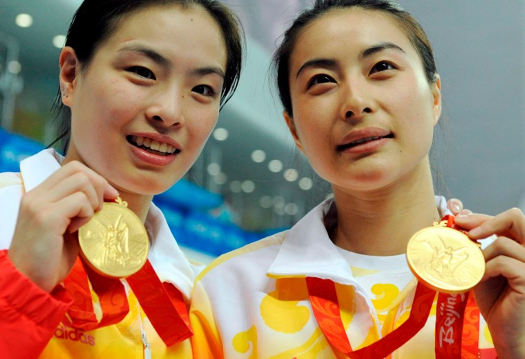 Image: Chinese divers Minxia Wu and Jingjing Guo show their gold medals