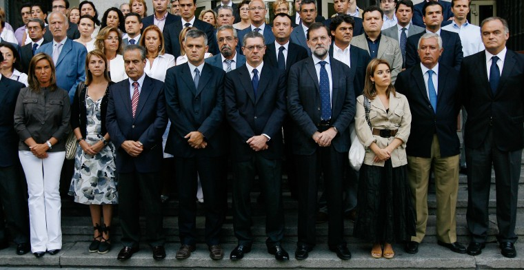 Image: Spanish politicians stand outside city hall to observe five minutes of silence in remembrance of victims of the Spanair plane crash in Madrid