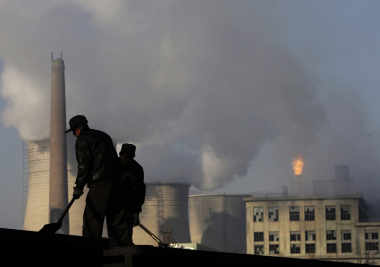 Workers in China's Hebei province on Nov. 30shovel coal used by the power plant and chemical factory behind them. Coal-fired power plants are amajor source of carbon dioxide emissions.