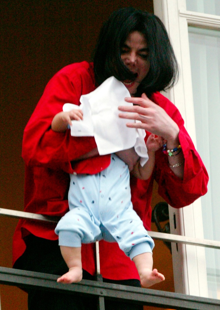 Image: Michael Jackson holds a child out of a window at a Berlin hotel