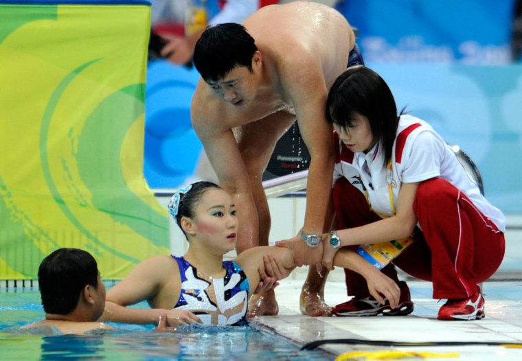 Image: Hiromi Kobayashi of Japan is helped out of the pool
