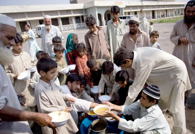 Pakistani people from the Bajur tribal region receive donated food Saturday in a vocational school building on the outskirts of Charsadda, Pakistan. It's one of more than 20 relief camps the government says are for displaced people.