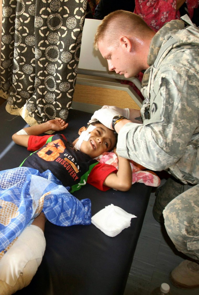 Image:  U.S. soldier attends to a boy who was wounded