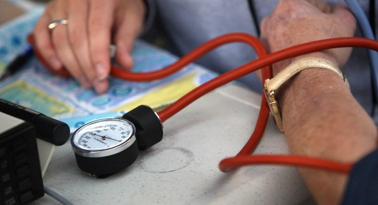 Image: A nurse checks a patient's blood pressure