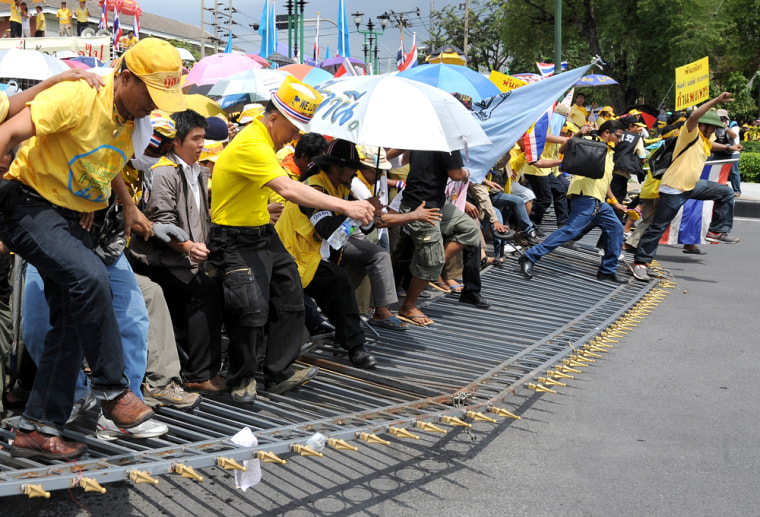 Image: Anti-government protesters break barricades during their entry into Government House in Bangkok, Thailand