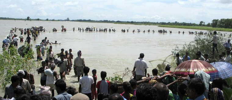Image: Flood-affected local residents wade through an overflowing Koshi river