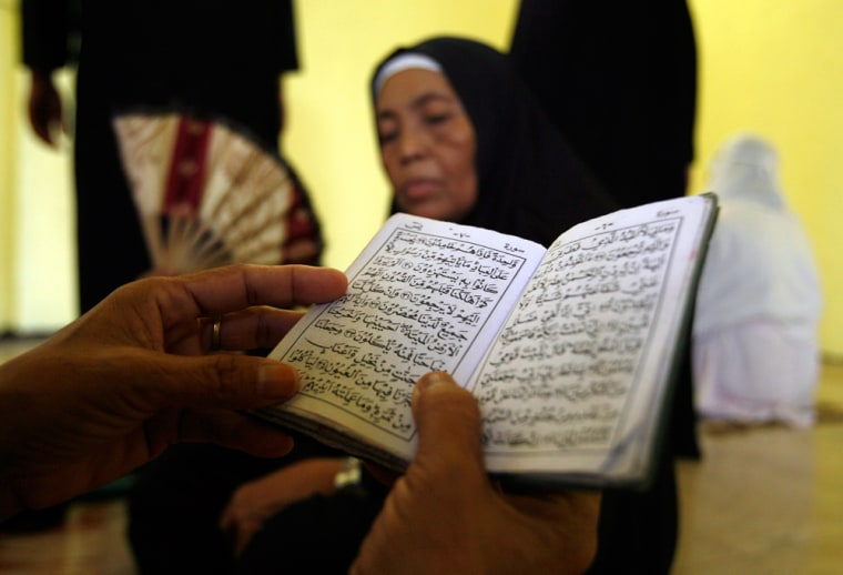 Image: A Muslim woman reads Koran during prayer session marking the start of Ramadan at the Golden Mosque in Manila