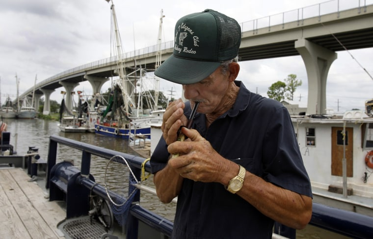 Image: Oneal Foret lights his pipe aboard the transport boat in Houma, La.