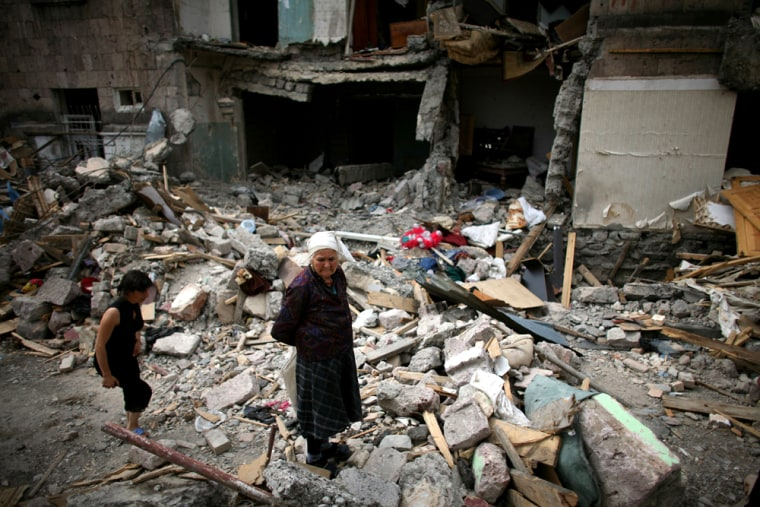 Image: Georgian women walk next to a bombed building in Gori, Georgia.