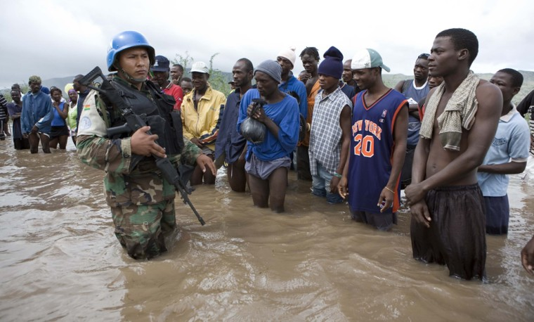 People stand in an area flooded by heavy rains from Tropical Storm Hanna