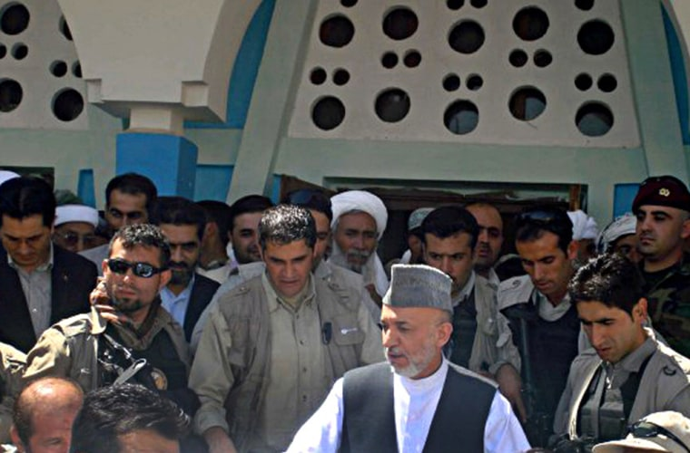 Image: Afghan President Hamid Karzai arrives in the village of Azizabad