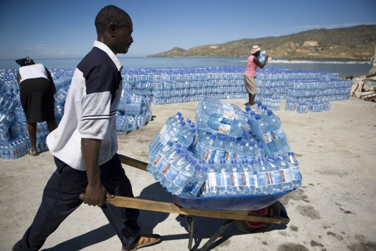 A man carries bottles of water donated by the Word Food Program in Gonaives, Haiti, on Friday.