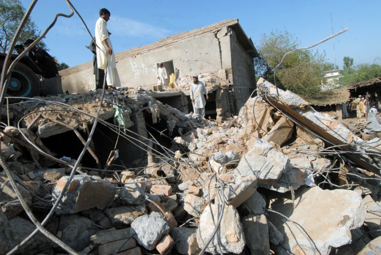 Image: Pakistani area residents inspect a destroyed building a day after a suicide attack in Peshawar