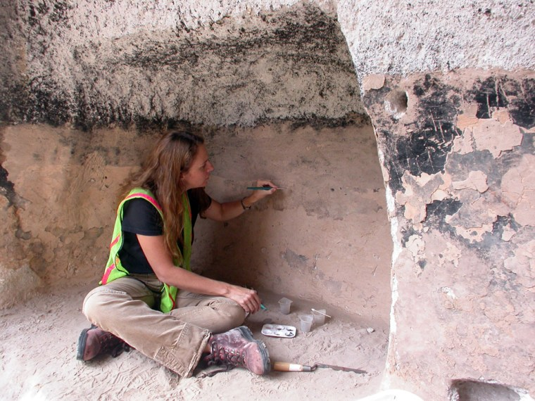 Image: NPS conservator Angelyn Bass Rivera inpaints soil fills to obscure graffiti carved into the walls of a cavate in Frijoles Canyon at Bandelier National Monument
