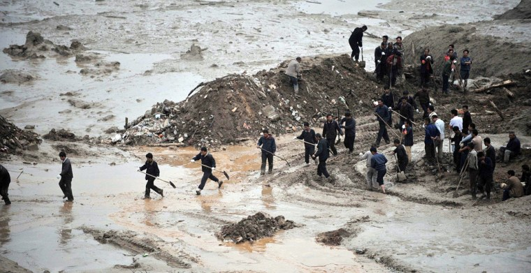 Image: Rescuers search for survivors after a mud and rock slide
