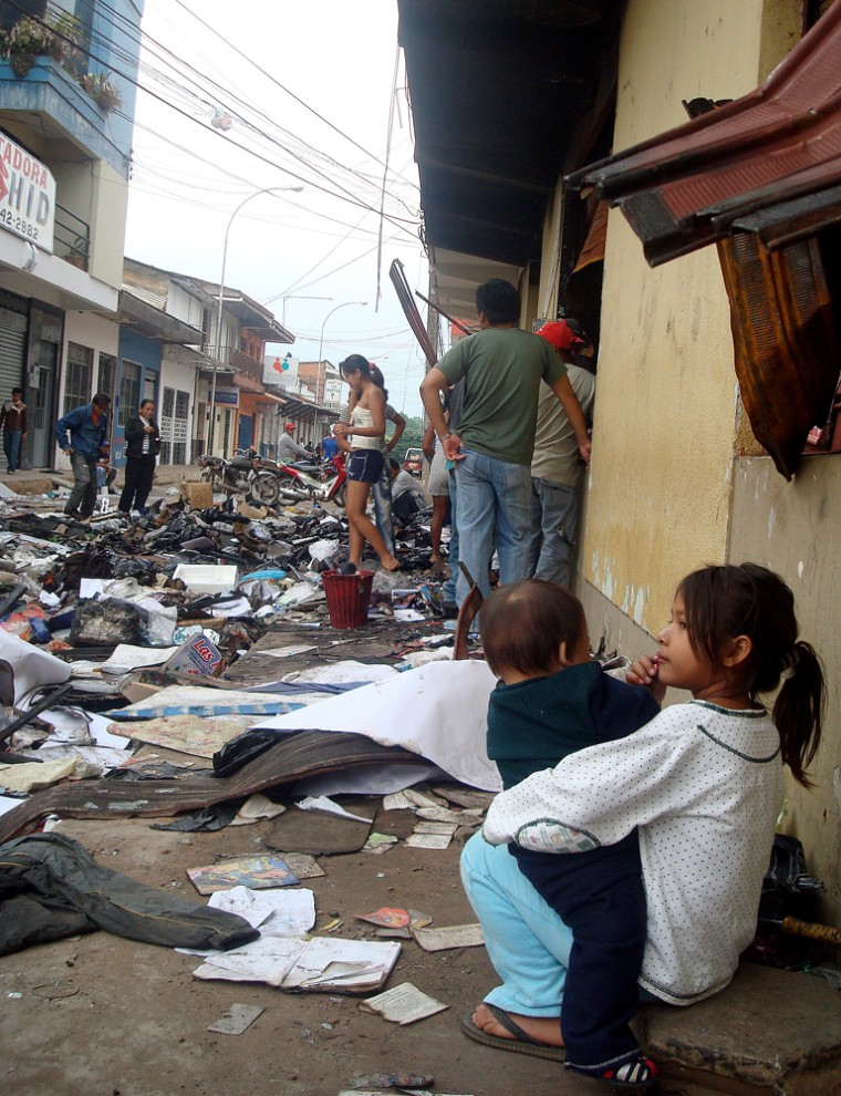 People survey damage on street where stores were looted by protesters in Pando province