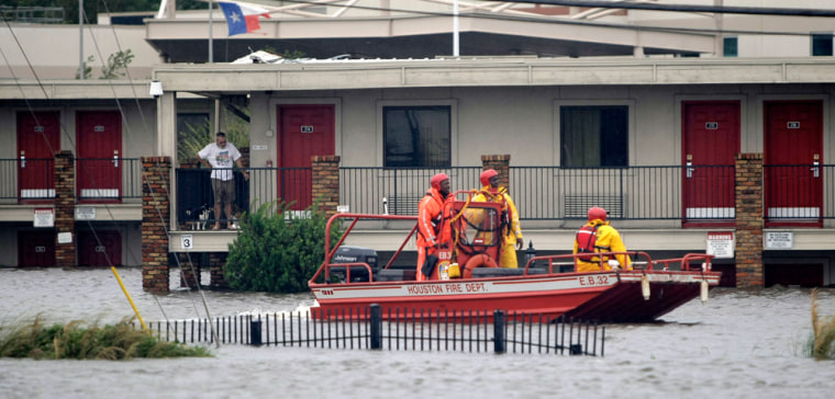 Image: Houston Fire Department members in a rescue boat look for people in need of rescue