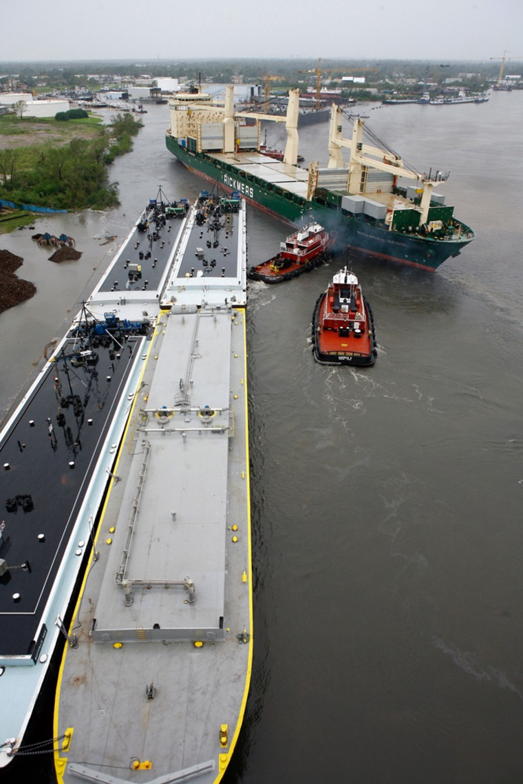 Image: Tugboats work to move a ship away from an oil barge in the Houston Ship Channel where ships and Port of Houston traffic were affected by the storm surge and winds of Hurricane Ike