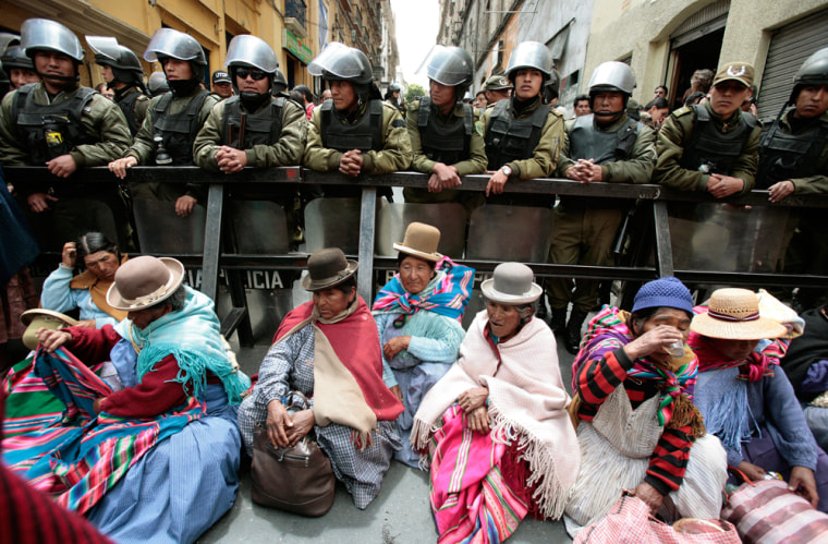 Image: Indigenous supporters of Bolivia's President Evo Morales sit in front of police standing guard next to the Congress building in La Paz