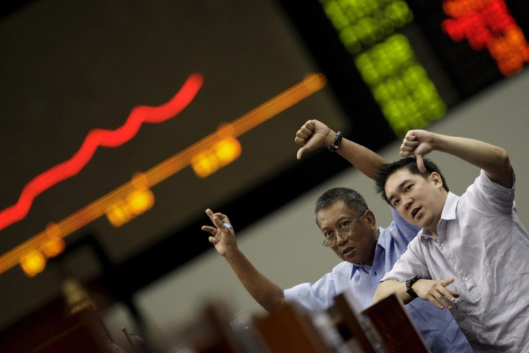 Image: Filipino traders display thumbs down signs in front of the Philippine Stock Exchange trading board