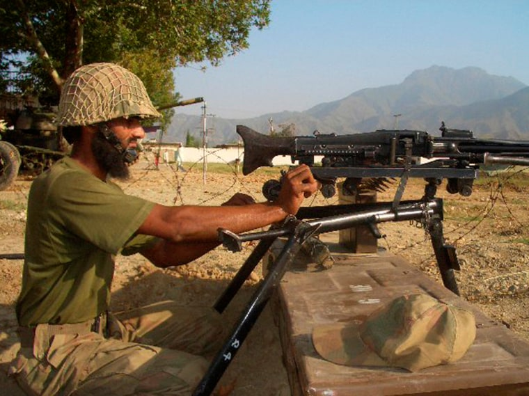 Image: A Pakistan soldier mans a machine gun  in the troubled area of Bajur