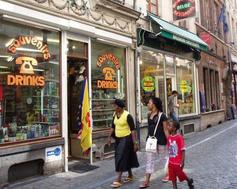 Image: Tourists walk past a telephone shop in the Brussels city center