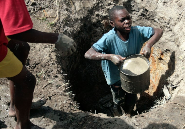 Image: A young boy lifts a bucket filled with ground water in Harare, Zimbabwe