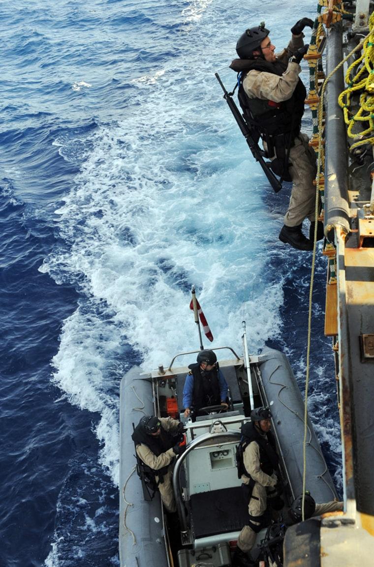 Image: A Canadian Navy sailor climbs on the World Food Programme cargo ship